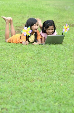 third world: Picture of young girls from the third world (south asia) learning the technology from a laptop computer in green grass outdoor environment