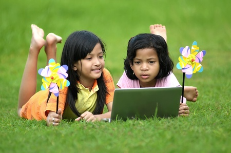 Picture of young girls from the third world (south asia) learning the technology from a laptop computer in green meadow