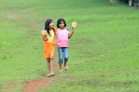 Beautiful friendship moments. Two girls walking on a green meadow. They are  best friends and sharing a story together. Stock Photo - 12029942