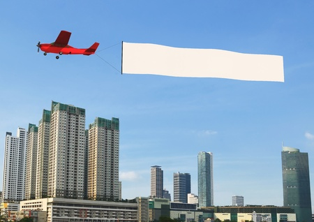 Airplane banner pulled by airplane flying over a modern city building