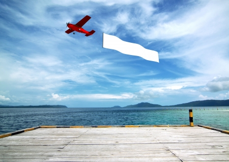 advertise: Airplane banner pulled by airplane flying over a beautiful tropical beach