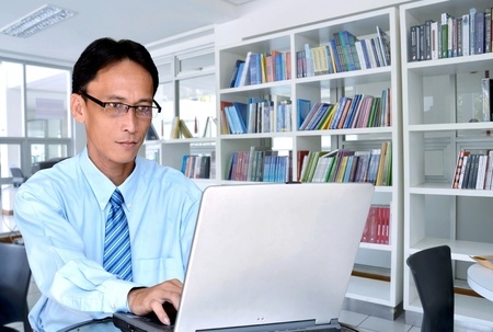 master degree: A businessman or a lecturer  or a master degree student using laptop for work or doing a research on a laptop inside a modern library  study  room  Stock Photo