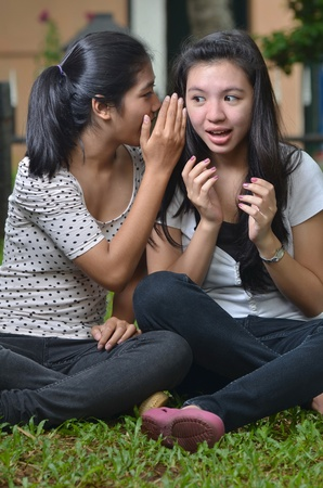 girl friends: Two pretty southeast asian girls sharing exciting stories   gossiping  whispering to ears  with excitement at outdoor scene Stock Photo