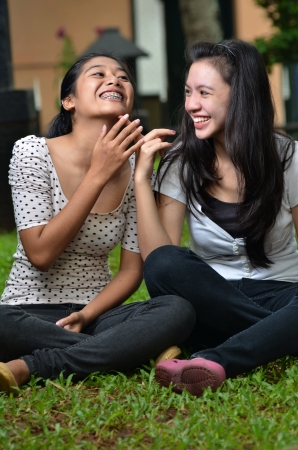 Two pretty southeast asian girls sharing exciting stories   gossiping  with excitement at outdoor scene Imagens