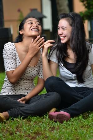 Zwei hübsche südostasiatischen Mädchen teilen spannende Geschichten Klatsch bei Erregung mit Outdoor-Szene Standard-Bild - 15155112