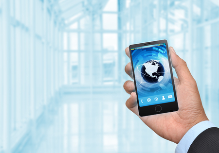 in need of space: Businessman hand holding a generic smart phone with modern interioir background You can change the phone screen easily  to suit your need or use the left part of image as your copy space  Stock Photo