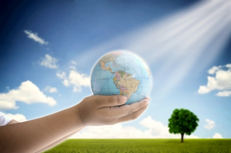 A conceptual image of a boy holding the earth globe with his two hand  A symbol of hope, future generation and  saving envronment legacy for future generation  photo