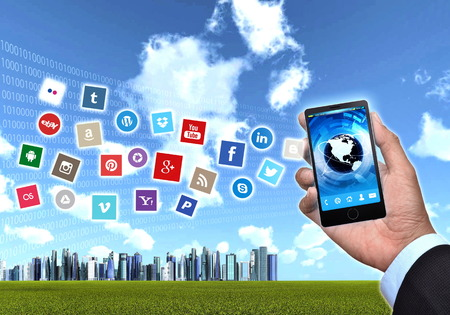background skype: A generic smart phones hold by a businessman hand showing famous social media application  icon