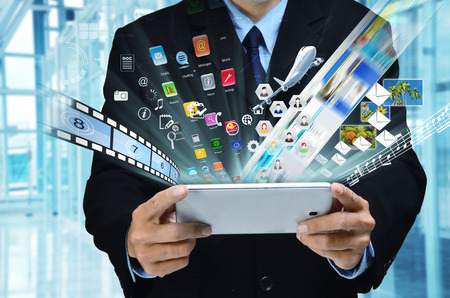 A businessman accessing internet and information technology via tablet   gadget in his hand