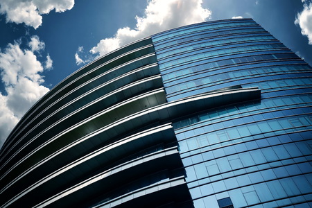 construction companies: Modern and futuristic commercial business building with blue sky background from street point of view