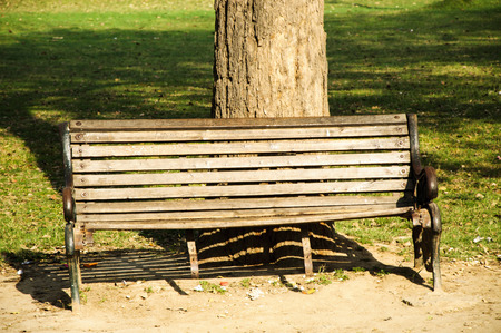A very lonley wooden bench in the park