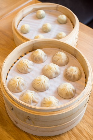 chinese steamed bun in bamboo steamer on wooden table stock photo