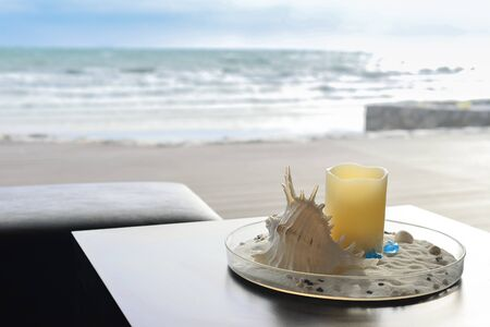 swimming candles: near beach decoration with shell and candle on sand tray Stock Photo