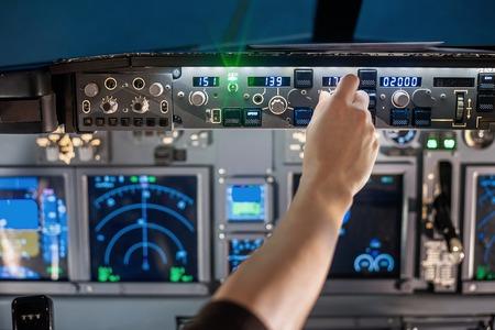 critics: man hand operate switch on airplane panel Stock Photo