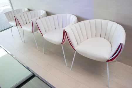 row: white stylish chairs in a row Stock Photo