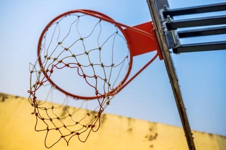 Basketball hoop under yellow wall & blue sky