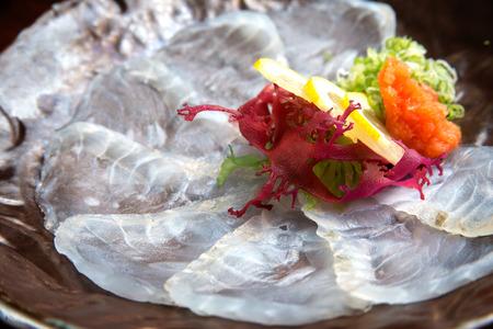 White fish sashimi of dark plate