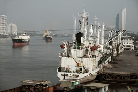moor: White Cargo ship moor at pier on chaow pra ya river - Bangkok Thailand Stock Photo