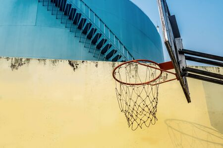 Basketball hoop over yellow wall & blue Giant water tower