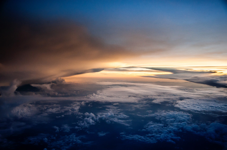 Aerial view of a cloudy sunset while flying above the clouds Reklamní fotografie