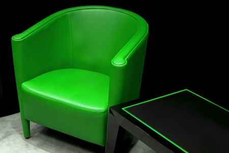Empty green chair over black wall