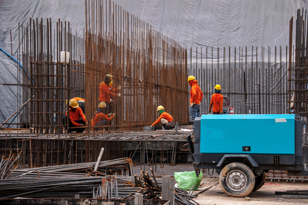Construction workers working on steel rods used to reinforce concrete