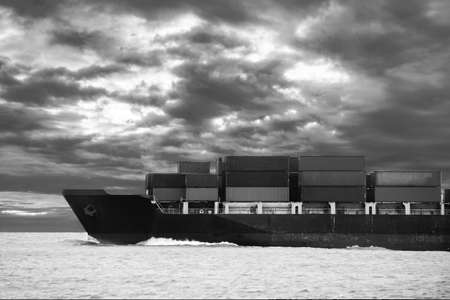 Cargo ship travel on the ocean with cloudy sky background Standard-Bild