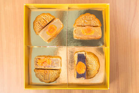 4 moon cakes in a Chinese mid-autumn festival in golden box and cut up half to show egg yolk