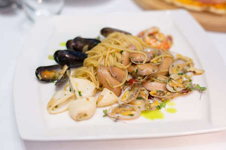 seafood spaghetti - Italian stir fried noodle with squid , clam , mussel and prawn with olive oil and herb on white plate