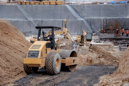 Road roller working in factory construction site foudation.