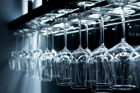 Group of empty wine glasses hanging from metal beams. Stock Photo