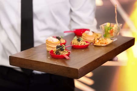 Waiter serve canape selection on slate wooden platter Standard-Bild