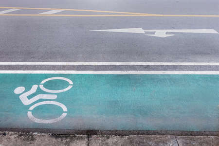 Green bike lane on city street and direction arrow