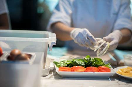 Female chef is preparing vegetable in kitchen