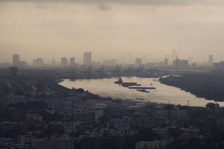 Morning moment of bangkok river bend with cityscape and industrail docks
