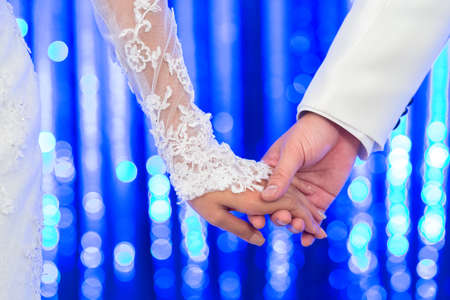 bride and groom holding hand in wedding ceremony with glitter background
