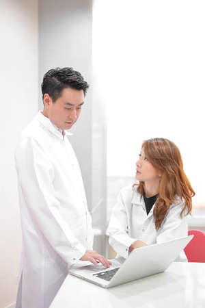 two young attractive (Asian)  doctors talking with look in computer Banque d'images