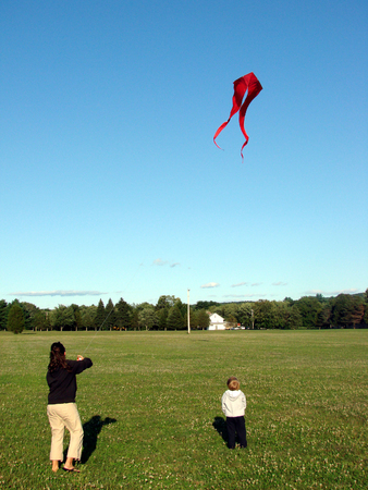 A woman shows her son how to fly a kite