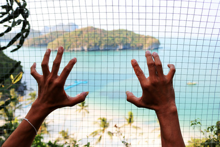 The hand holding the steel mesh with blurry background image view of ang thong island.