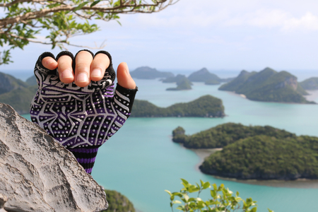 Rock Climbing,Hands with gloves on the mountain at the viewpoint Angthong island.