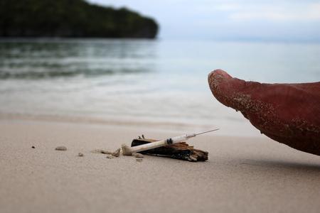 Voetstap op injectienaalden op het strand.