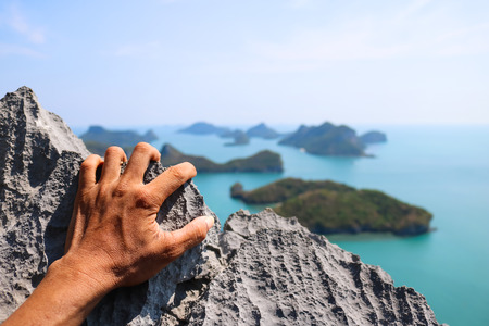 Hands climbing the rock at the viewpoint Angthong island. Stock Photo