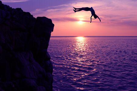 filles asiatiques sauter d'une falaise dans le coucher du soleil de l'épisode de la mer, culbute à l'océan