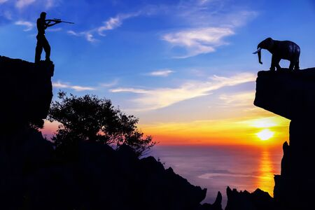dissolve: Men shooting elephants, The model of elephants with men use gun,Background image of sunset on the mountains Stock Photo