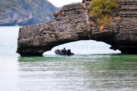 Man driving a boat under a stone that looks like bridge.