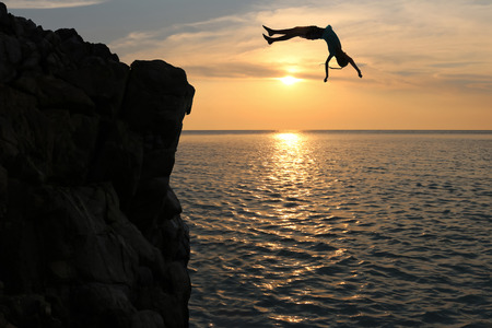 Asian girls jump from a cliff into the sea episode sunset,Somersault to the ocean Stock Photo