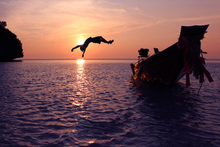 episode: The girls jump from a boat into the sea episode sunset,Somersault to the ocean Stock Photo