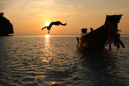 The girls jump from a boat into the sea episode sunset,Somersault to the ocean Stock Photo