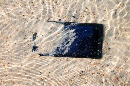 The Phone  camera fall to the water on the beach.