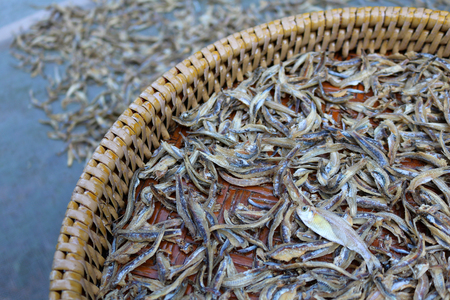 Dried salted fish on the wicker baskets.
